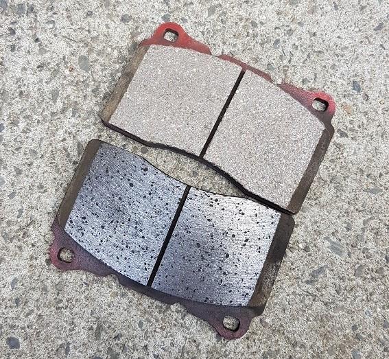 Przykład nowych i przegrzanych klocków hamulcowych ze spieczoną powierzchnią cierną